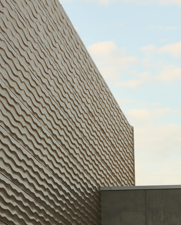 Die Fassade der Sporthalle Herdorf: Lochmetall-Fassadenplatten und Beton