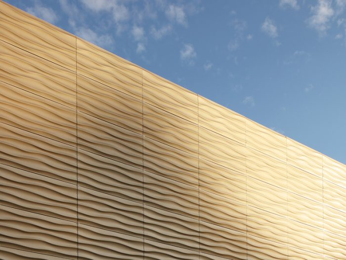 Metal façade of the Herdorf sports hall with light and shadow effects.