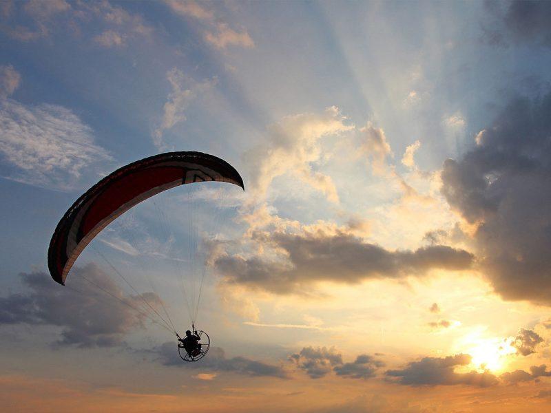 Paraglider against sunny sky